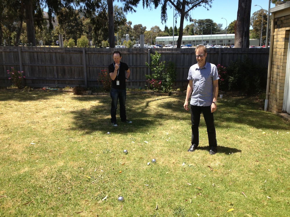 Matt and Kim observing Pétanque, with a view of the Monash Campus in the background.
